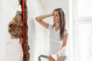 A stressed woman with a hole in the wall