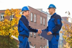 Two HVAC technicians shaking hands